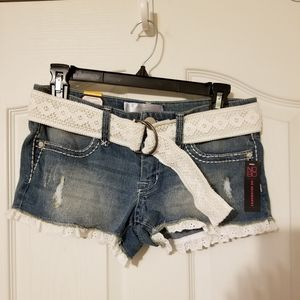 Distressed denim shorts with cotton lace detail.